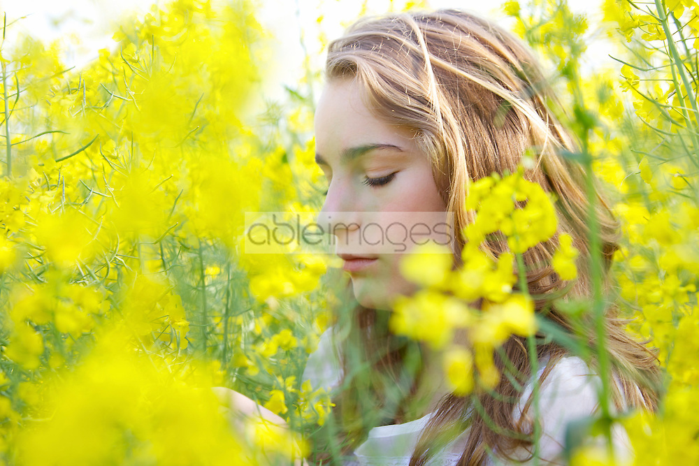 Profile of Young Woman amongst Canola Flowers