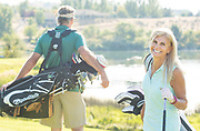 Senior couple golfing, woman turns to smile while walking and carrying bags in the canyon at the public course, Clear Lakes Country Club in Buhl, Idaho. MR