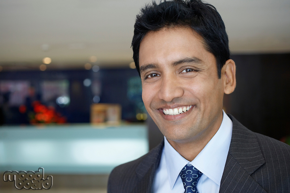 Business man standing in hotel lobby portrait close up
