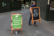 As the UK's Conornavirus pandemic lockdown continues, but with travel restrictions and social distancing rules starting to ease after three months of closures and isolation, a man carries a No Entry sign at Borough Market whose food stalls are slowly opening up again for business after months of lockdown, on 9th June 2020, in south London, England.