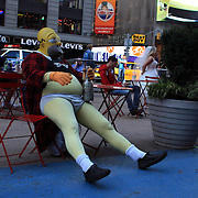 An entertainer dressed as Homer Simpson in Time Square, New York. Times Squares' costumed entrepreneurs are officially free to ply their trade without fear of retribution.  The entertainers are allowed to receive tips, but not charge for pictures taken with them in costume. Times Square is the major commercial intersection in Midtown Manhattan. Time Square, New York, USA. 27th April 2012. Photo Tim Clayton