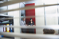 Business colleagues discussing document in office seen through window blinds
