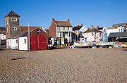 Fishing boats on the beach, Aldeburgh, Suffolk, England. Disused lifeboat building and look out tower.