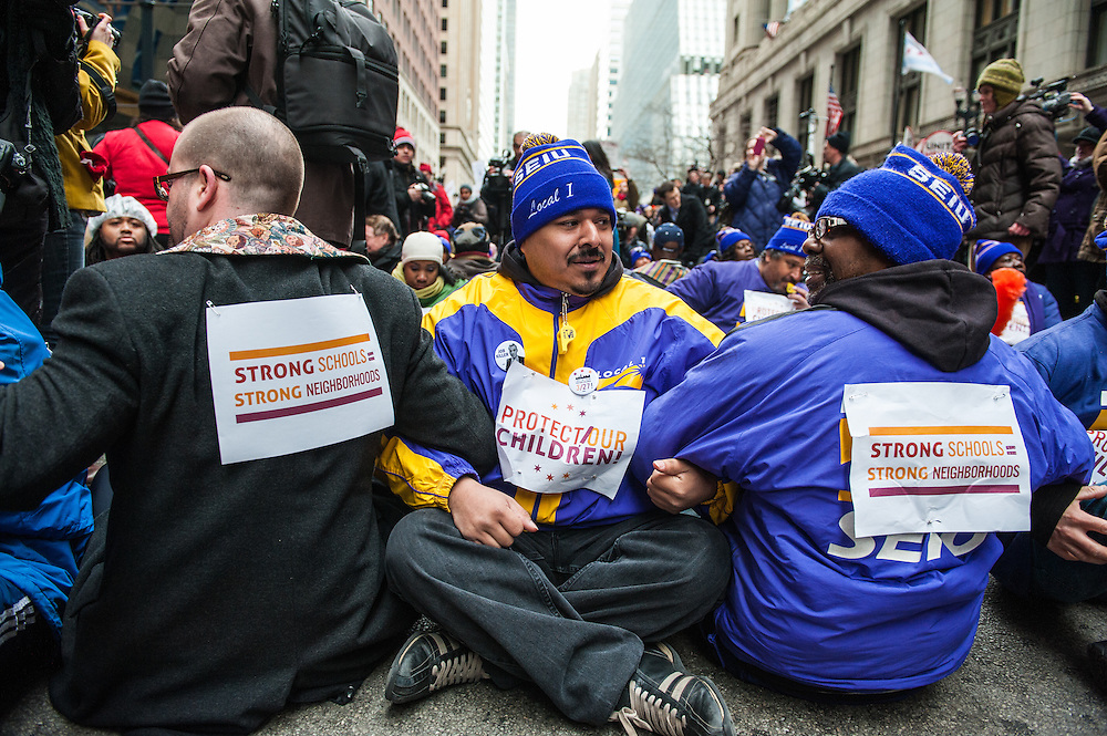 Protestors sit in front of Chicago Public Schools headquarters in opposition of the closing of 53 Chicago public schools.