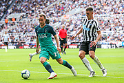 Christian Eriksen (#23) of Tottenham Hotspur on the ball under pressure from Ciaran Clark (#2) of Newcastle United during the Premier League match between Newcastle United and Tottenham Hotspur at St. James's Park, Newcastle, England on 11 August 2018.