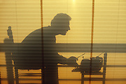 Man typing on vintage typewriter seen through window shade at sunset/sunrise.
