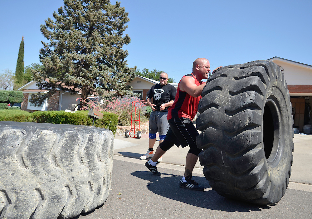 JD070811c/Sports/07.09.11/Jessica Dyer.Ty Roberts, right, and John Posen train together for strongman competitions by flipping large tires in the street in front of Posen's Albuquerque home..Albuquerque, New Mexico(Albuquerque Journal)