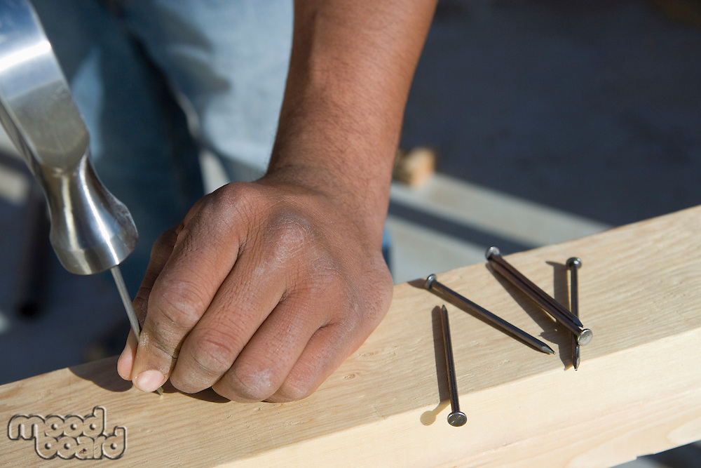 Man hammering nails to wooden plank