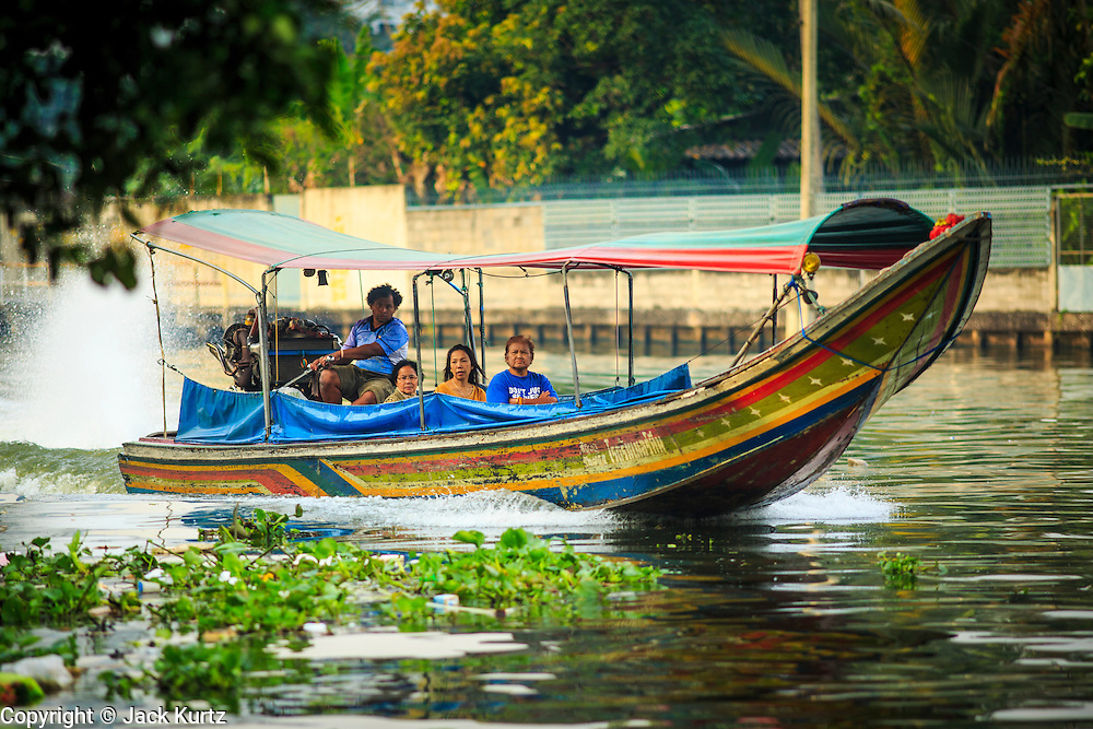 04 JANUARY 2012 - BANGKOK, THAILAND:  A longtailed boat takes passengers up Khlong Phra Khanong past Wat Mahabut in eastern Bangkok. The temple was built in 1762 and predates the founding of the city of Bangkok. Just a few minutes from downtown Bangkok, the neighborhoods around Wat Mahabut are interlaced with canals and still resemble the Bangkok of 60 years ago. Wat Mahabut is a large temple off Sukhumvit Soi 77. The temple is the site of many shrines to Thai ghosts. Many fortune tellers also work on the temple's grounds.   PHOTO BY JACK KURTZ