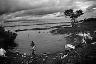"""A Warao woman returns from bathing in the Orinoco river. Warao means, """"people from the rivers edges"""". In an effort to escape poverty, hunger and to be closer to health care facilities, approximately 300 Warao indigenous persons from the Delta Amacuro have settled in Ciudad Guayana, in northeastern Venezuela. The Warao sustain themselves and their families by salvaging recyclables, clothing and discarded food in Cambalache, located minutes from downtown Ciudad Guayana. Although Warao community leaders say their quality of life is improved in comparison to the conditions in the Delta, the Warao are still plagued by hunger and diseases consequential of the unsanitary conditions of living and working in Cambalache."""