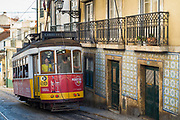 Historic famous number 28 tram carrying local people and tourists driving on tram tracks up a steep hill in Lisbon, Portugal