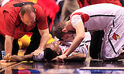 Louisville player Luke Hancock, right, tries to comfort teammate Kevin Ware after Ware broke his leg in the first half of action against Duke. The Louisville Cardinals faced the Duke Blue Devils in the NCAA Men's Regional basketball Final at Lucas Oil Stadium on Sunday, March 31 2013. (Mike Fender / The Star)