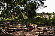 A boy from Srae Sronok carving poles out of tree trunks which are gonna be used to build a new house in the relocation site. Like many others, he refuses to move into one of the several concrete houses provided by the government since there have been concerns about the building quality.