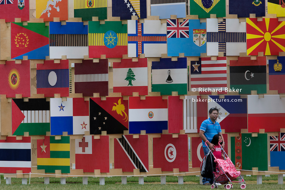 Foreign family visitors for the 2012 Olympics admire the 'House of Flags' a structure of 206 panels containing the flag icons of all the countries participating in the London 2012 Olympics and Paralympics. Designed by AY Atchitects, the structure is opposite the Palace of Westminster in Parliament Square.