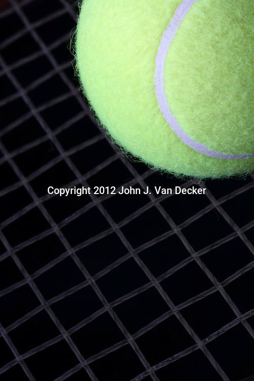 Tennis anyone? A close-up of a tennis ball and racket strings.