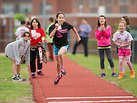 Madison Carignan of Elm Street School is cheered on by her competitors from Woodland Heights and Pleasant Street Elementary Schools during for high jump during the 5th grade track meet Wednesday morning at Opechee Park.  (Karen Bobotas/for the Laconia Daily Sun)