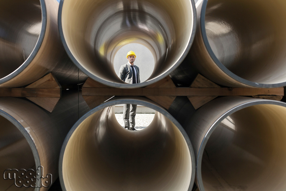 Full length of young male architect through stacked pipes at construction site