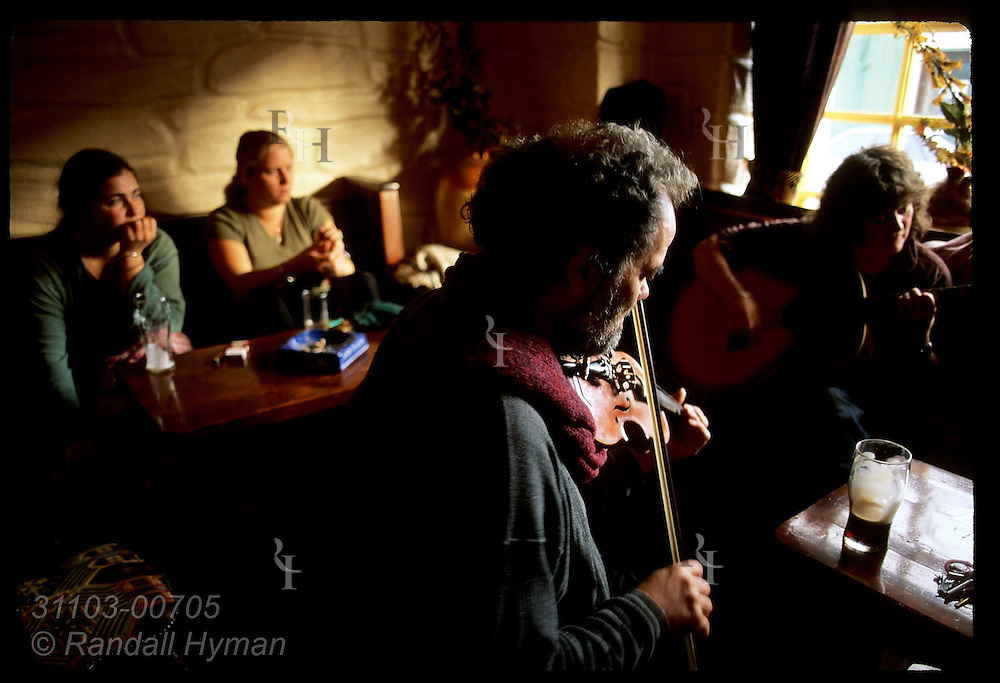 Fiddler Mike Venner and a guitarist perform in Barr Na Sraide pub; Dingle, Ireland.