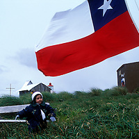 Chile, Isla Hornas, Jennifer Sepulveda Quintrileo, 2, daughter of lighthouse keeper, sits atop windswept Cape Horn