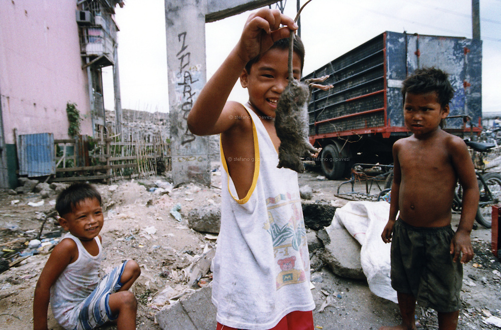 Philipphine , Manila , March 1999 - In the &quot; smoky mountains &quot; people lives by picking-up and selling the rubbish - Children with a rat corpse.<br /> <br /> Operation Smile is a private, not-for-profit volunteer medical services organization providing reconstructive surgery and related health care to indigent children worldwide.