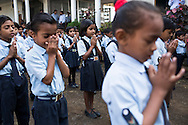 Anjali Kanel (centre), aged 6, says a prayer together with other children during morning assembly in the Vasudha Vidya Vihar school in Khargone, Madhya Pradesh, India on 12 November 2014. Anjali is the daughter of a Fairtrade cotton farmer and her ambition is to be a Computer Engineer. This school was built using the Fairtrade Premium funds of the Fairtrade cotton farmers and producers in Karhi village of Khargone. Photo by Suzanne Lee for Fairtrade