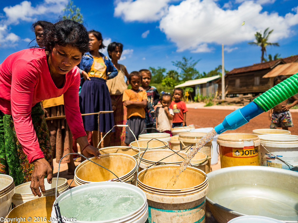 03 JUNE 2016 - SIEM REAP, CAMBODIA: A woman picks up her just filled water jug at a water distribution point in Sot Nikum, a village northeast of Siem Reap. Wells in the village have been dry for more than three months because of the drought that is gripping most of Southeast Asia. People in the community rely on water they have to buy from water sellers or water brought in by NGOs. They were waiting for water brought in by truck from Siem Reap by Water on Wheels, a NGO in Siem Reap. Cambodia is in the second year of  a record shattering drought, brought on by climate change and the El Niño weather pattern. There is no water to irrigate the farm fields and many of the wells in the area have run dry.     PHOTO BY JACK KURTZ