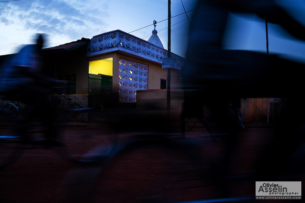 Bicycles drive by a mosque in Tamale, northern Ghana on Tuesday March 24, 2009.