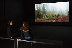 "© Licensed to London News Pictures. 24/09/2018. LONDON, UK. Staff members sit next to a work called ""BRIDGIT"" showing iPhone recordings of the Scottish countryside.  Preview of an exhibition unveiling the four artists shortlisted for Turner Prize 2018 at Tate Britain. The exhibition is open 26 September to 6 January 2019.  Photo credit: Stephen Chung/LNP"