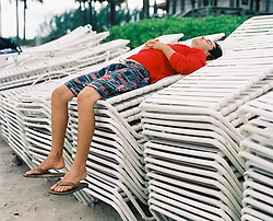 man relaxing on stack of lounge chairs
