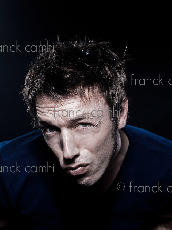 studio portrait on black background of a funny expressive caucasian man frowning suspicion