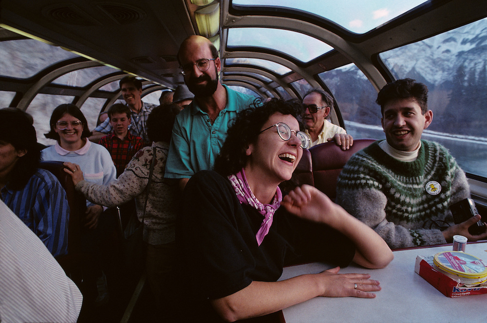 Canada, Alberta, Tourists watch Rockies from dome car aboard VIA Rail passenger train near Lake Louise