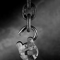 black and white open lock hanging from a chain