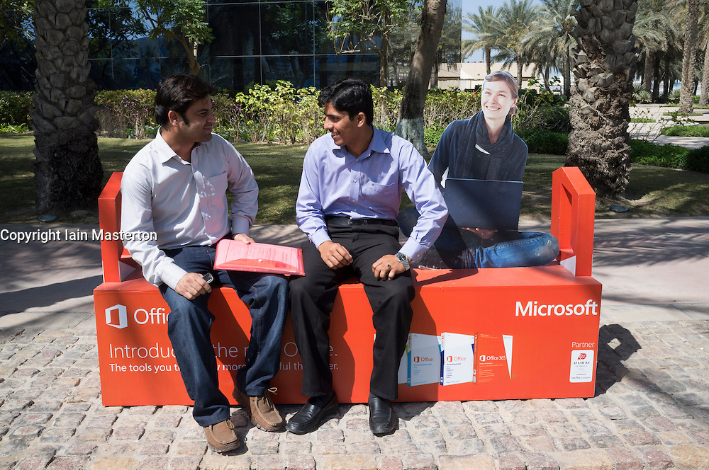 Two workers sitting on bench advertising Microsoft at Dubai Internet City in United Arab Emirates UAE