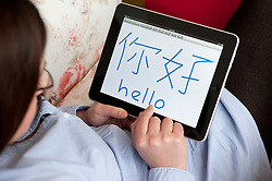 Woman learning to write Chinese characters  on an iPad tablet computer