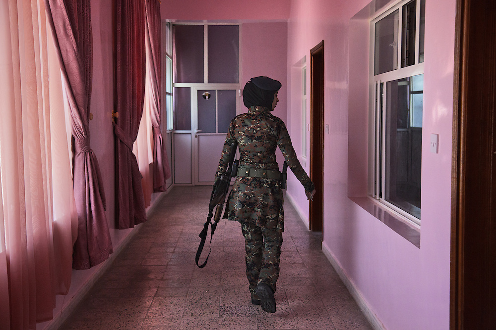 "A lieutenant patrols the pink barracks of Yemen's female counterterrorism unit at a base in Sana, Yemen, Nov. 13, 2012. ""The color on the walls was our idea,"" says one officer. ""We fought for the color."" Some 1,500 women serve in police and counterterror units. They're crucial in an ultraconservative culture where men cannot check female suspects, or those disguised as women."