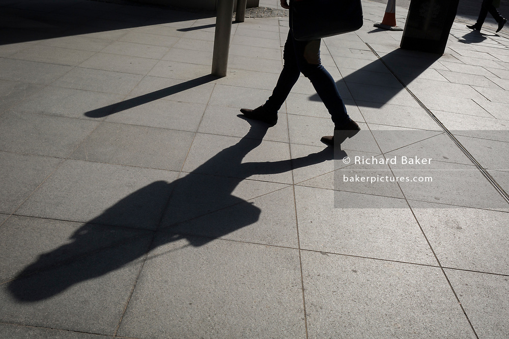 Striding Legs and long shadows on Lime Street in the City of London - the capital's financial district, on 3rd September 2018, in London England.