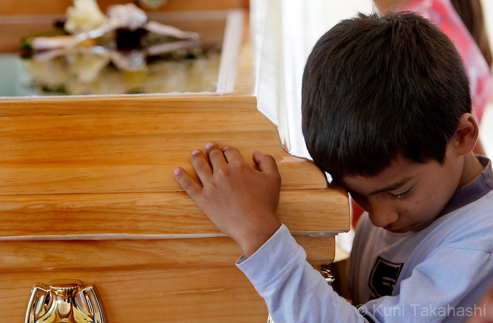 Rodrigo de la Torre, 8, embraces a casket of his mother, Mariana, during her funeral in Apatzingan, Mexico on April 8, 2009. (Photo by Kuni Takahashi)