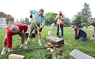 Joe Konecny (from left) of Cedar Rapids, Mike Papich, of Cedar Rapids, Stanley Ditch, of Ely, and Roman Zach, of Swisher, work on resetting sinking headstones during the annual Join Hands Day at the Czech National Cemetery, 2200 C St SW in Cedar Rapids on Saturday morning, May 5, 2012. The Join Hands Day was organized by local CSA Fraternal Life and WFLA lodges. (Stephen Mally/Freelance)