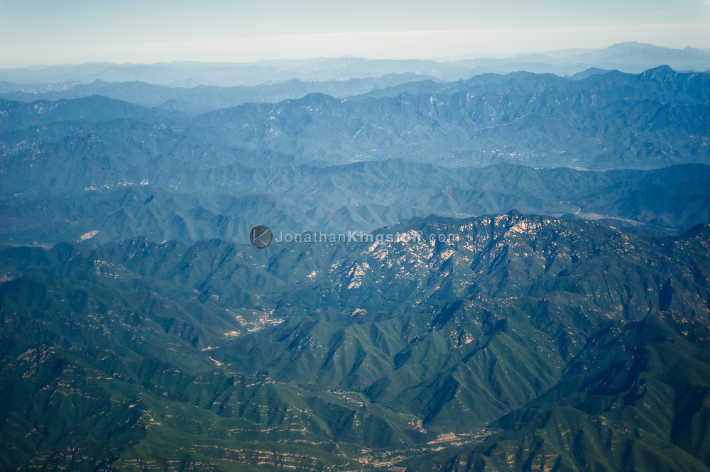 Aerial view of mountains near Beijing, China.  The Great Wall of China is barely visible in the background.