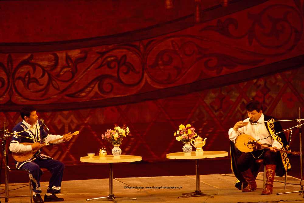 A first-rate Aytis, a performance competition between singers/poets known as Aqins, contains the essence of theater-the element of agame, the circle of experience, knowledgeable spectators and the highest level of mastery by the performers.  The Aytis underway here is the annual competion in Almaty held at the Palace of the Republice