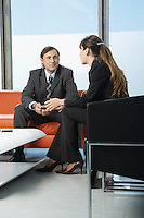 Business man and woman talking in office waiting area