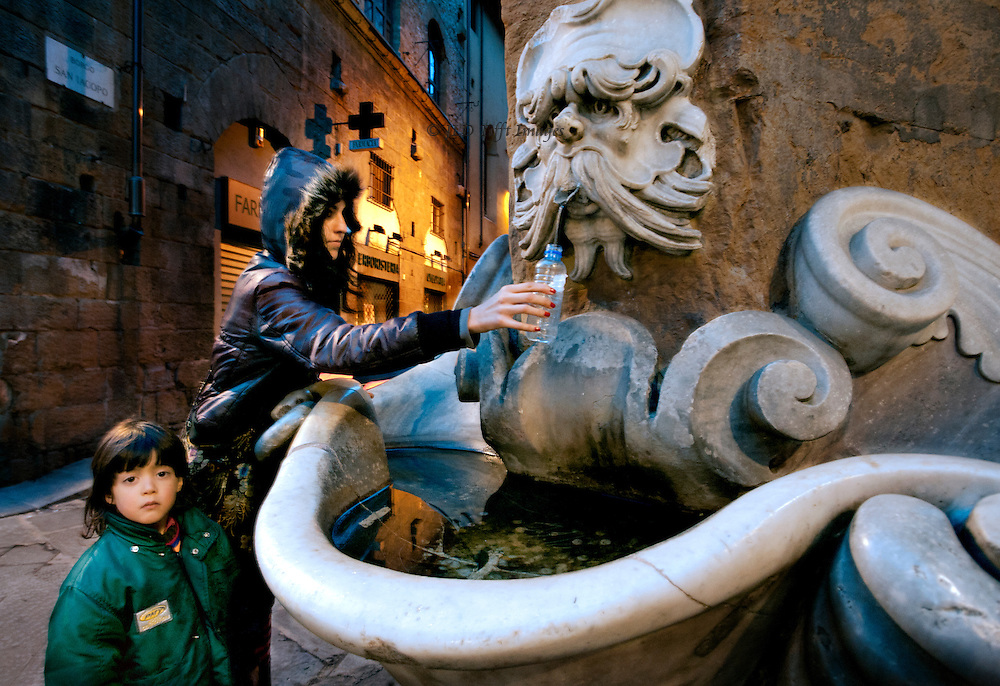 A Florentine woman, with her young daughter (about six years old), fills a water bottle at a Baroque wall fountain in the Oltrarno.  Both wear padded jackets.  The fountain, on a street corner, has above it a grotesque mask.  The fountain is shaped in swoops and scrolls, echoed in her curved arm reaching out, and curving fur hood of her jacket.