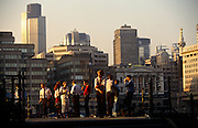 A group of work colleagues, friends and associates gather on a sunlit terrace with a backdrop of the City of London on the opposite, northern shore of the River Thames. People stand with drinks in their hands in the evening summer sunshine and we see the tall Natwest tower and other banking institutions plus the much older Monument on the far right, commemorating the Great Fire of London in 1666, when the old Elizabethan city was burned to the ground, making way for the newer metropolis. But the architecture we see here is largely from the 1980s building boom of the Thatcherism era.