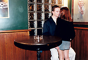Young woman standing in between young man's legs in pub.