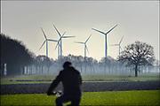 Nederland, Zeddam, 14-2-2017Uitzicht op windmolens in het buitengebied van de Achterhoek terwijl een man op de fiets voorbijfietst.Foto: Flip Franssen