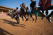 Group of boys jumping up in the air as they warm up prior to a football practice in Accra, Ghana.