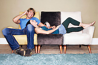 Young Couple sitting lying on sofa Listening to MP3 Player