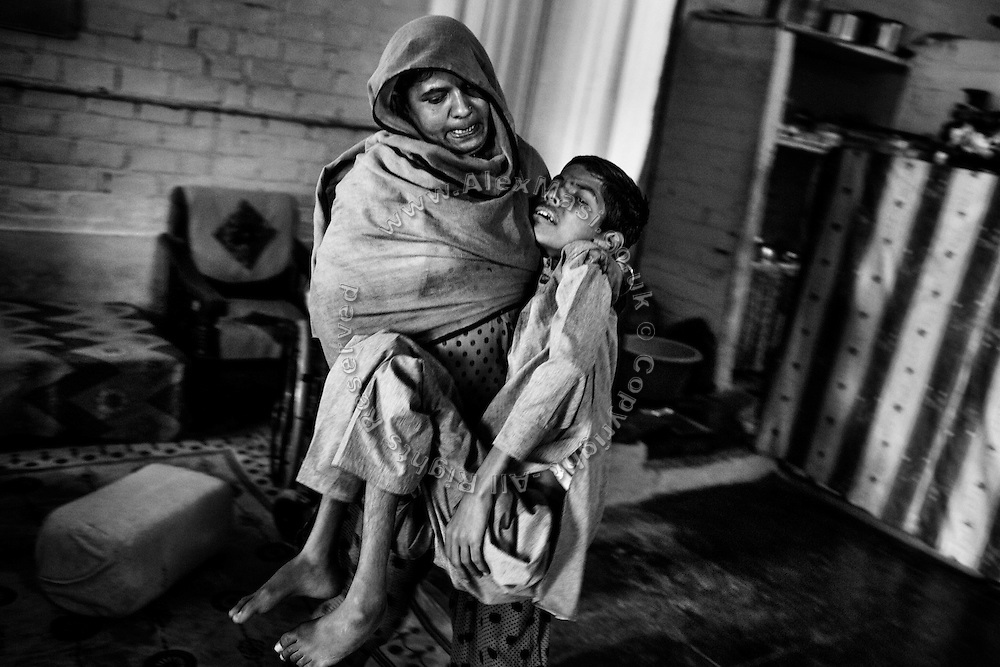 With great effort, Farida Sultan, 44, a '1984 Gas Survivor', is lifting Azhar, 16, one of her two severely disabled sons affected by severe muscular dystrophy, while inside their home in Shahjahanbad, Bhopal, Madhya Pradesh, central India.