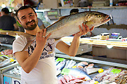 A fish monger holds up a freshly caught fish in the fish market, Fethiye, Turkey