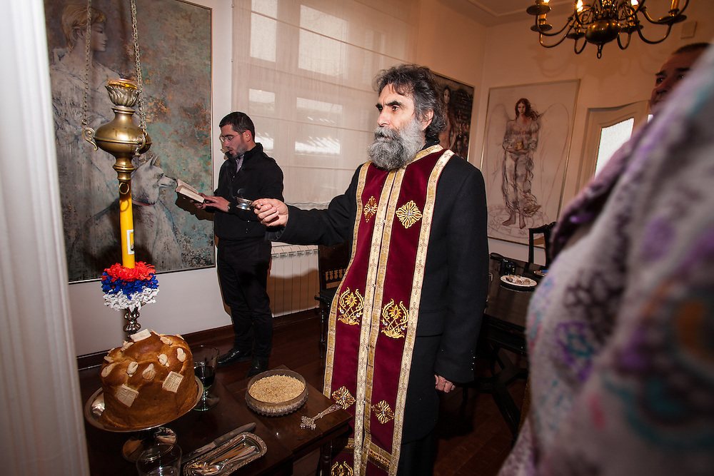 Radivoj Panic, Serbian Orthodox Priest from Saint Sava Cathedral, blessing the bread, wine and zito for a Saint Jovan (Saint John the Baptist) Slava celebration at a private home in Belgrade, Serbia.